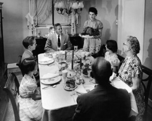 family-sits-at-a-formally-prepared-dinner-gettyimages-610x484